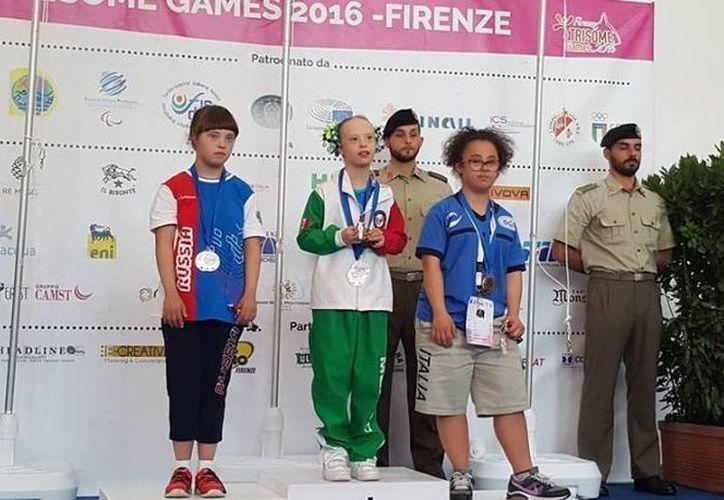 La mexicana Bárbara Wetzel (c) ya ganó cinco preseas en gimnasia en los Juegos de la Trisomía. (Foto tomada del Facebook de Bibi)
