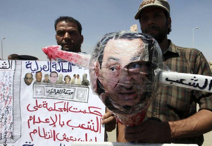 Un manifestante egipcio sujeta una efigie del expresidente Hosni Mubarak con una flecha atravesada, durante una protesta frente a la Academia de Policía. (EFE)