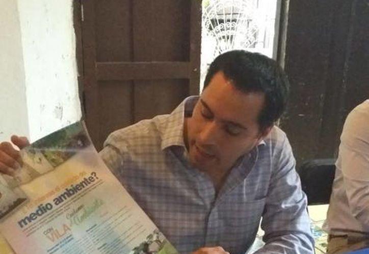 El diputado Mauricio Vila Dosal con el cartel en el que se promociona su segundo concurso de dibujo con tema del medio ambiente. (Cortesía)