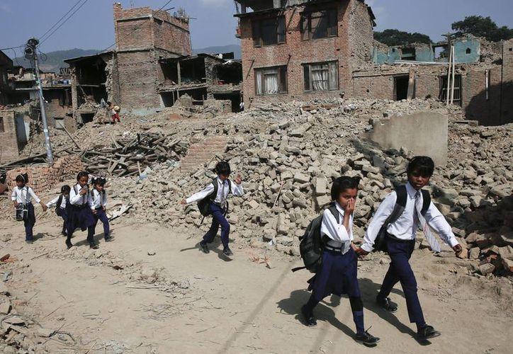 Varios niños pasan por una zona arrasada por el terremoto de camino al colegio en Bungmati, Katmandú, Nepal. (EFE)