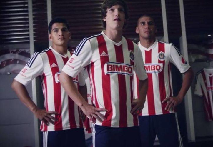 Jesús Sánchez (i), Carlos Fierro (c) y Carlos Salcido aparecen modelando la nueva playera de Chivas de Guadalajara. (Captura de pantalla de YouTube)