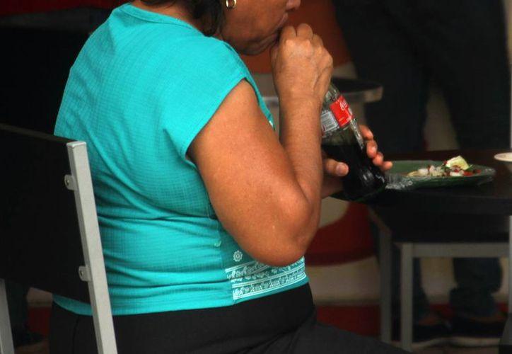 Las personas sedentarias presentan otros hábitos de vida perjudiciales, como fumar, consumir comida rápida y refrescos embotellados. Imagen de contexto de una mujer mientras toma una Coca-cola. (Milenio Novedades)