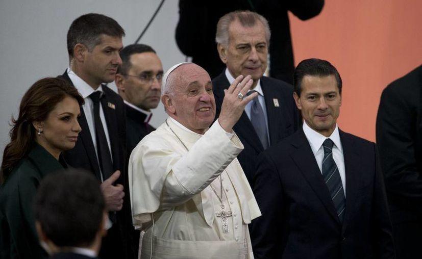 Papa Francisco saluda a los asistentes en Palacio Nacional. En la imagen se le ve junto al presidente de México, Enrique Peña Nieto y su esposa Angélica Rivera. (Agencias)