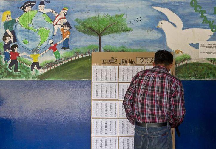 Un hombre busca su nombre en el registro electoral para ubicar su mesa de votación en la localidad de Panchimalco, El Salvador. (Agencias)