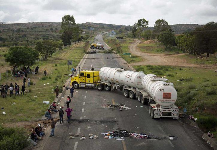 La inseguridad y el asalto a camiones ha provocado que no se surtan los productos en Oaxaca. Imagen de los bloqueos carreteros que hay en Oaxaca. (Agencias)