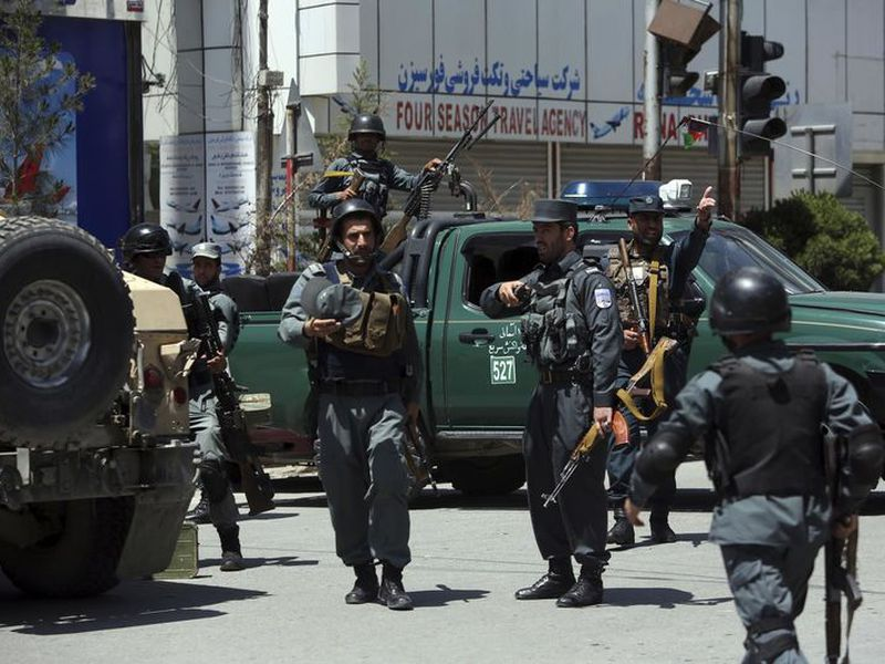 Afghan security personnel inspect the area of a suicide attack in the center of Kabul, Afghanistan. Three suicide bombers struck two police stations in Afghanistan's capital on Wednesday, wounding at least six people, officials said.