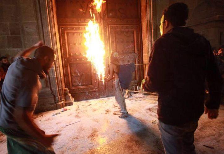 La noche del pasado sábado, una veintena de manifestantes escapuchados atacaron el Palacio Nacional, sede del Ejecutivo mexicano, y prendieron fuego a la puerta principal. (Foto EFE)
