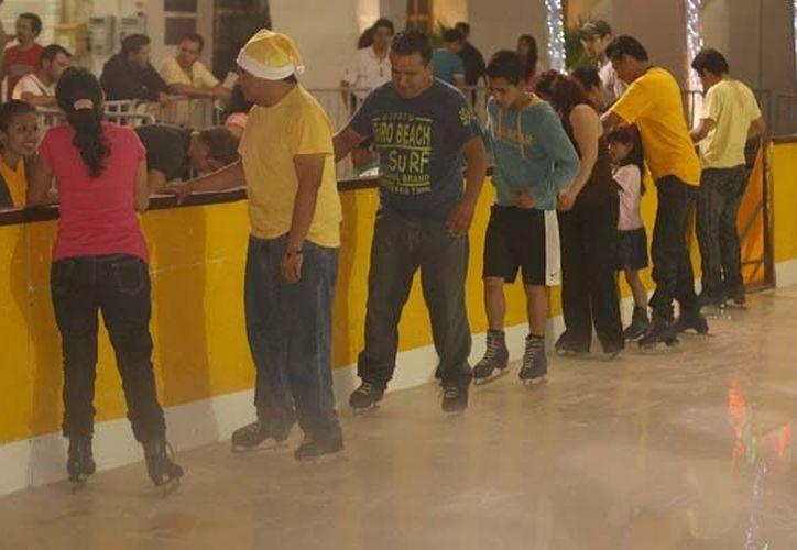 Jóvenes de diferentes instituciones educativas realizan su servicio social en la pista de hielo instalada en la Plaza de la Reforma. (Redacción/SIPSE)