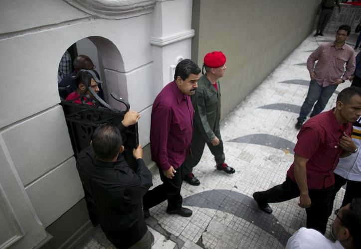 El presidente Nicolas Maduro sale del Palacio de Miraflores para encabezar un mitin con sus seguidores, en Caracas, Venezuela, el 28 de octubre de 2016. Este martes 1 de noviembre de 2016, el Parlamento decidió posponer la discusión sobre el juicio político al mandatario. (Foto de archivo AP/Ariana Cubillos)