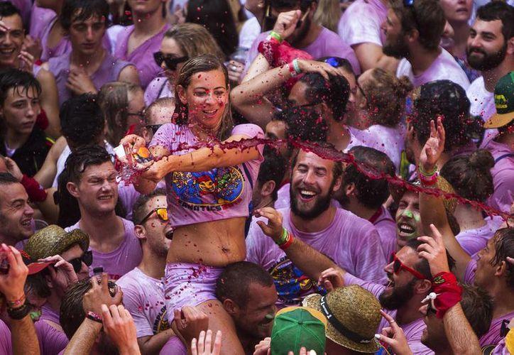 Una mujer lanza vino a los asistentes al 'Chupinazo' que da comienzo a las fiestas de San Fermín en Pamplona, España. (AP Foto/Andrés Kudacki)