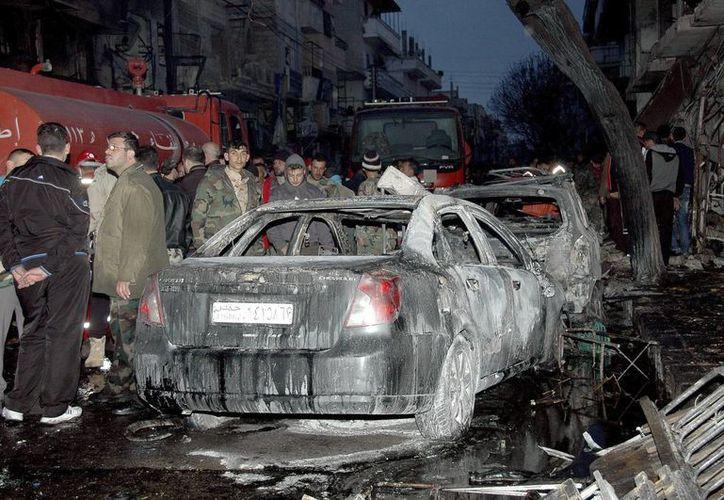 Miembros de la policía siria y varios ciudadanos inspeccionan los restos de los vehículos tras una explosión de un coche bomba en Homs, en el centro de Siria, hoy, lunes 17 de marzo del 2014. (EFE)