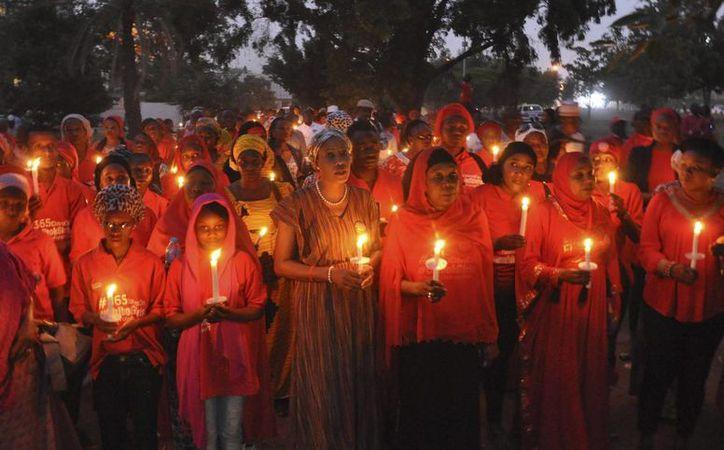 Varias mujeres nigerianas sostienen velas durante una vigila para pedir la liberación de las niñas secuestradas hace más de dos años en Chibok. (EFE)