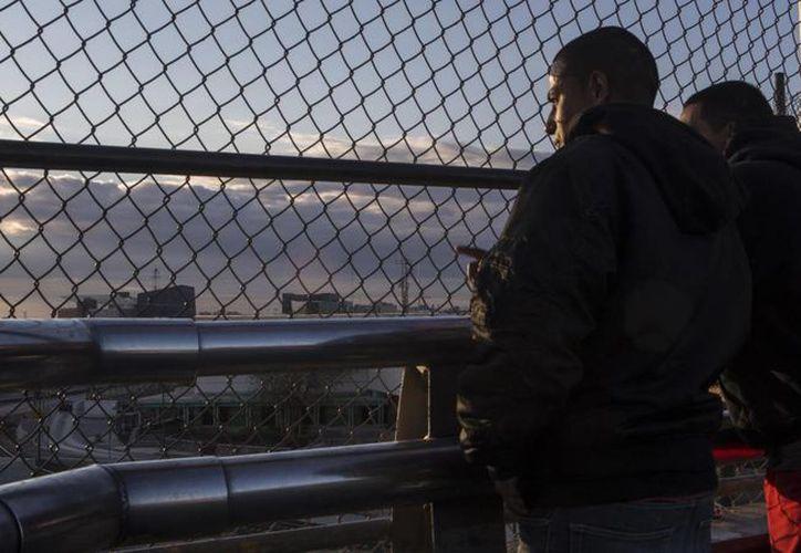 Ángel y David Castillo miran Estados Unidos a través del puente fronterizo. Con Trump en la presidencia, Ángel ha perdido la esperanza de obtener los papeles para estar legalmente en EU. (Christian Palma/internacional.elpais.com)