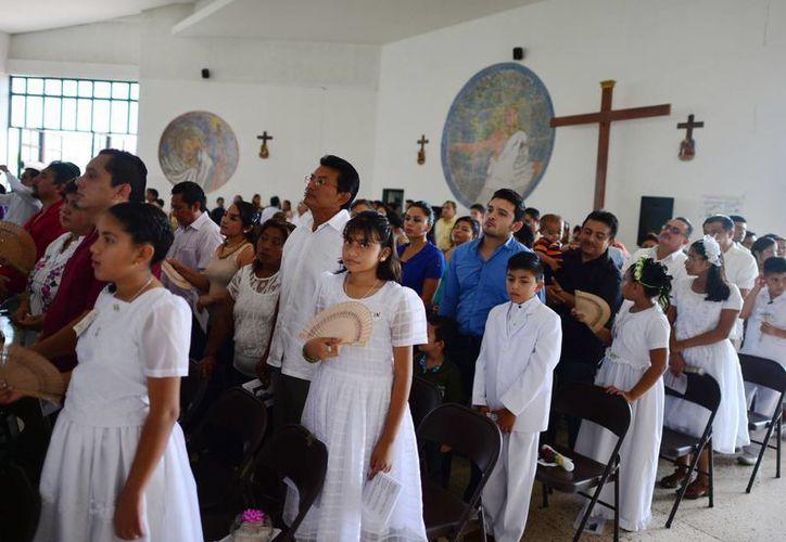 Un grupo de niños de San Juan Pablo II recibe la Confirmación, todos acompañados de sus padrinos. (Milenio Novedades