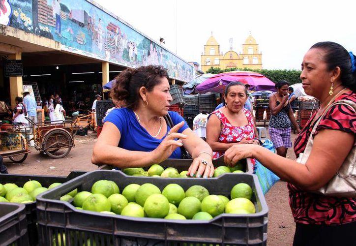 Imagen de dos mujeres en el mercado de Oxcutzcab, Yucatán, uno de los principales productores del cítrico en el Estado. (Milenio Novedades)
