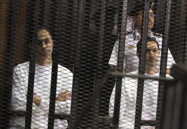 Foto de archivo de Gamal Mubarak (izq), y su hermano Alaa Mubarak, durante su juicio en Egipto. (Agencias)