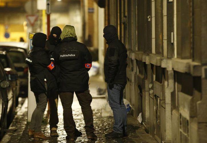 Policías vigilan la parte exterior de una casa registrada por la policía en el suburbio de Schaerbeek, en Bruselas, Bélgica, el viernes 25 de marzo de 2016. (Foto: AP)