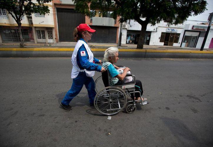 Un miembro de la Cruz Roja colombiana ayuda a un paciente a regresar al municipio de San Antonio, Venezuela. (Agencias)