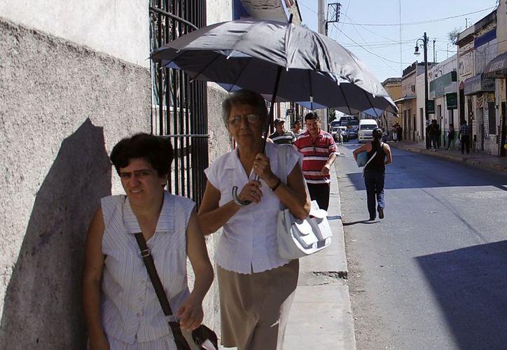Ayer domingo, algunos meridanos tuvieron que sacar las sombrillas para protegerse del sol. (Juan Albornoz/SIPSE)
