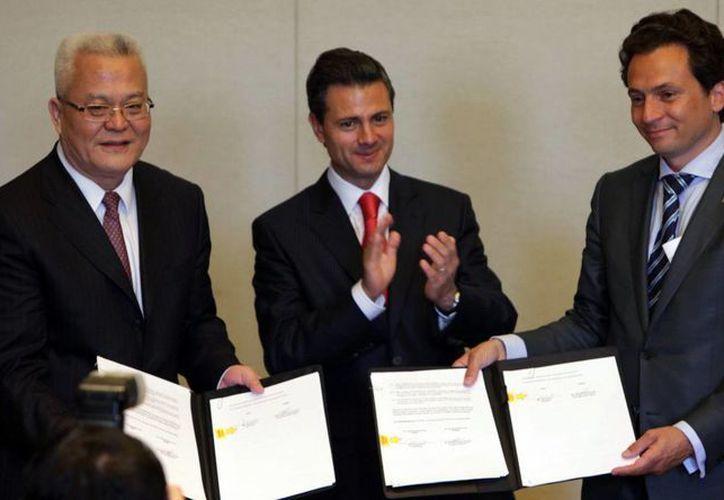 El representante de Sinopec, Peña Nieto y el director general de Pemex muestran el convenio firmado. (Notimex)
