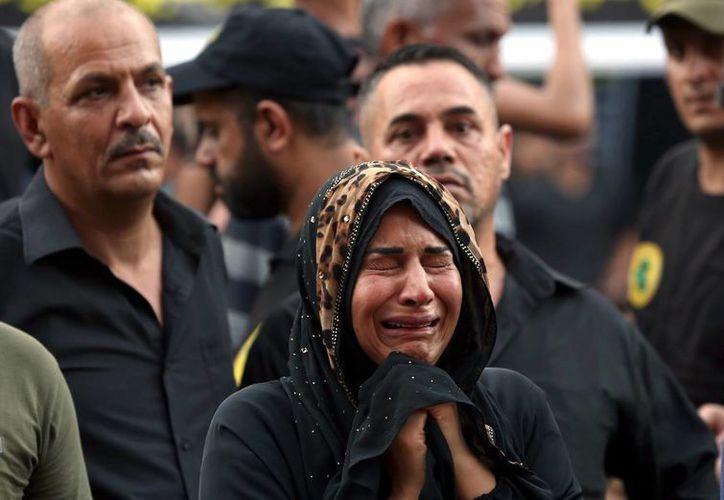 Una mujer llora durante el funeral de una víctima del ataque que ocurrió en el barrio de Karada de Bagdad. (Agencias)