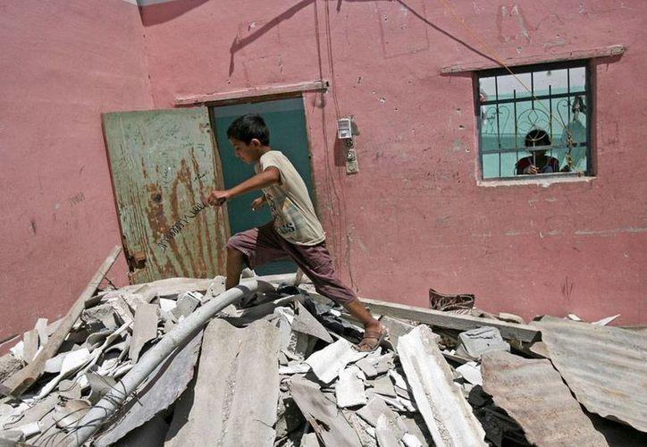 Un niño camina sobre los restos de una vivienda destruida por los intensos ataques de Israel en Franja de Gaza, poco antes de que se anunciara un cese al fuego. (AP)