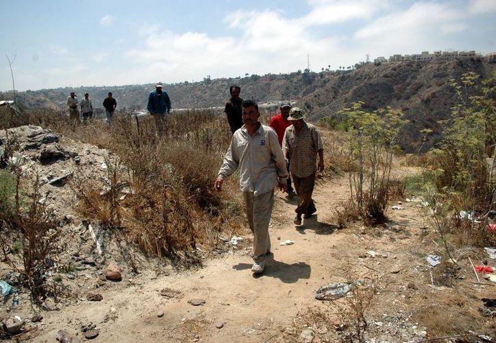 Migrantes se internan en una zona semidesértica muy cerca de la barda metálica que divide a México de Estados Unidos. (Notimex)