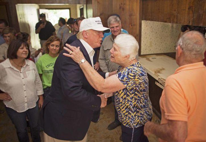 El republicano nominado a la presidencia, Donald Trump, consuela a una víctima de las inundaciones, Olive Gordan y su esposo Jimmy, durante una visita a la zona afectada, en Denham Springs, Louisiana, el viernes 19 de agosto del 2016. (AP Foto /Max Becherer)