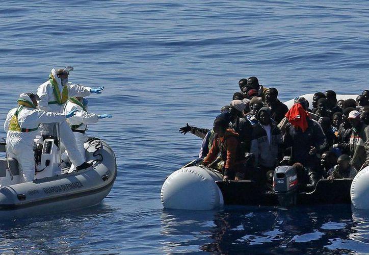 Imagen de un equipo de rescate de la policía italiana al aproximarse a una lancha llena de migrantes en aguas de Libia, en el mar Mediterráneo. (Alessandro Di Meo/ANSA via AP Photo)