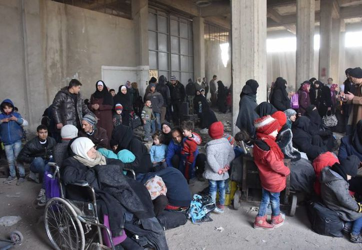 Fotografía cedida por la agencia Syrian Arab News Agency (SANA), que muestra familias de sirios desplazados desde Bestan al-Kasr y al-Ferdaws, en los barrios orientales de Alepo, a la espera de subir a unos autobuses para ser evacuados. (EFE)