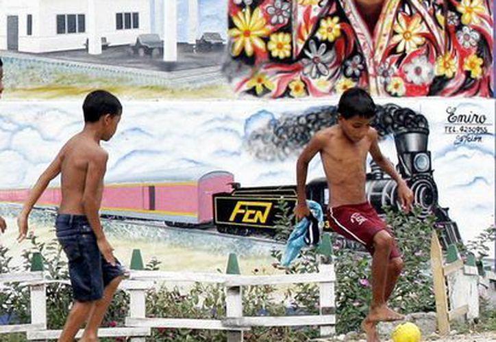 Un par de niños juegan futbol frente a un cartel del escritor colombiano Gabriel García Márquez, en la natal Aracataca del fallecido Premio Nobel de Literatura. (AP)