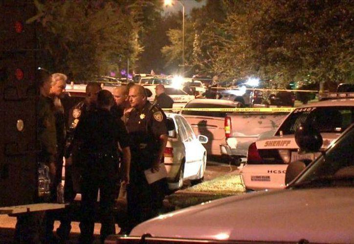 En esta imagen tomada de un video, la policía investiga la muerte de ocho personas en una vivienda de la zona de Houston después del arresto de un hombre que se tiroteó con la policía el 9 de agosto del 2015. (Foto via AP Video)