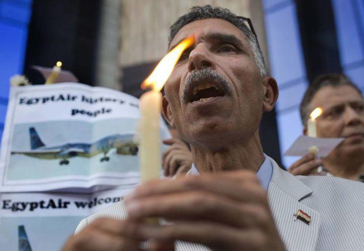 Un periodista egipcio sostiene una vela y un cartel de apoyo EgyptAir durante una vigilia por las víctimas del vuelo de EgyptAir 804. (Agencias)