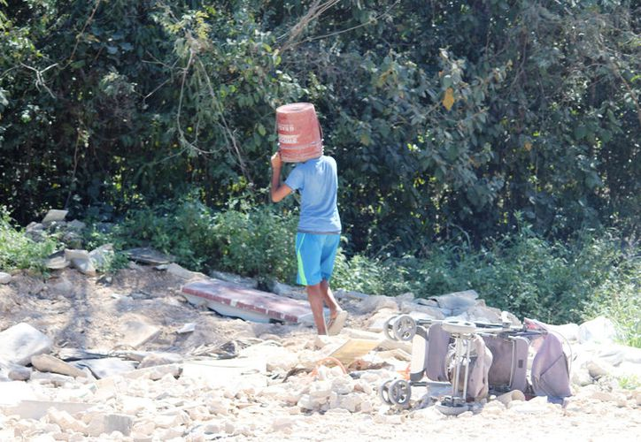 Los menores de entre ocho y 15 años, sacan tierra de las partes laterales del camino para rellenar los hoyos. (Foto: Octavio Martínez)