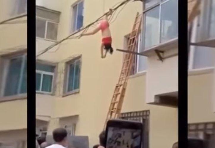 La mujer cuelga de un pie boca abajo de los cables de luz. (Foto: YouTube)