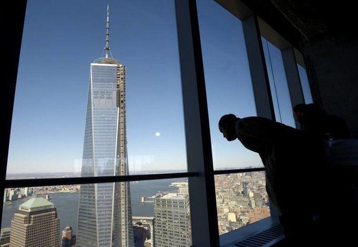 Un hombre se asoma desde lo alto del One World Trade Center, que aún es construido.  (EFE)