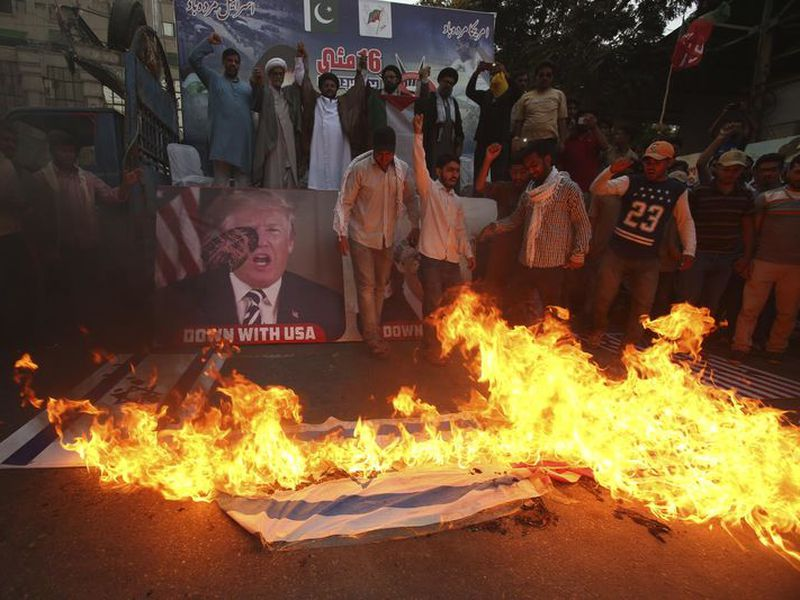 Pakistani Shiite Muslims burn representations of Israeli flags during a rally to protest the move of the U.S. embassy from Tel Aviv to Jerusalem, in Karachi, Pakistan.