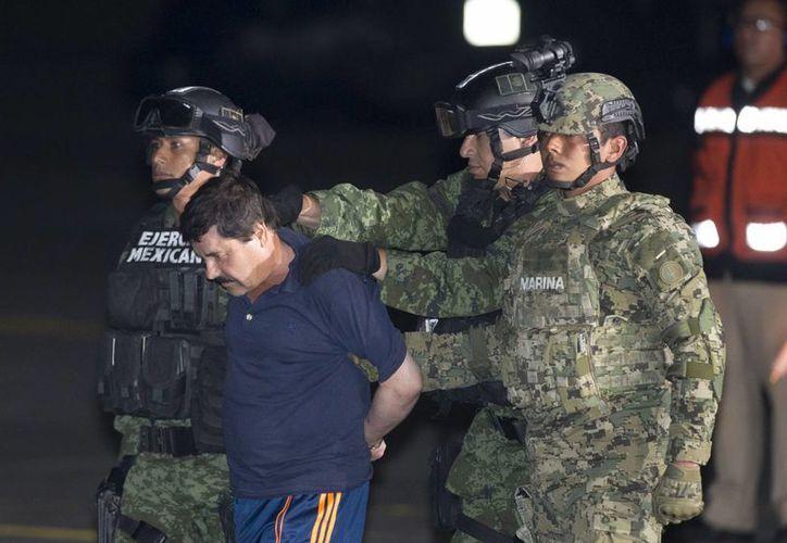"""Joaquín """"El Chapo"""" Guzmán al momento de ser escoltado hasta un helicóptero de la Marina en un hangar federal en la Ciudad de México. El proceso judicial de extradicción a EU en contra de El Chapo podría durar un año. (Foto AP / Eduardo Verdugo)"""