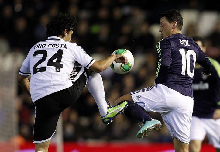 Mesut Ozil disputa el balón con Tino Costa (d), que anotó el gol del empate para el Valencia. (Agencias)