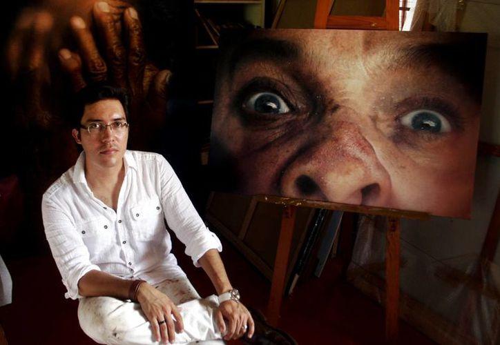 El pintor yucateco Jorge Ermilo Espinosa Torre muestra algunas de sus obras. (Christian Ayala/SIPSE)