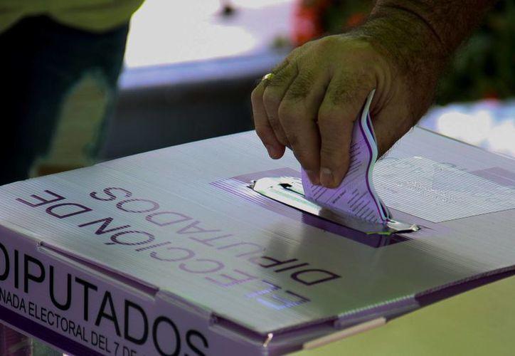 La encuesta encargada por la Cámara baja reveló que el 71 por ciento de la población asegura que hay corrupción en las campañas. Imagen de una persona votando en elecciones pasadas. (Archivo/Notimex)