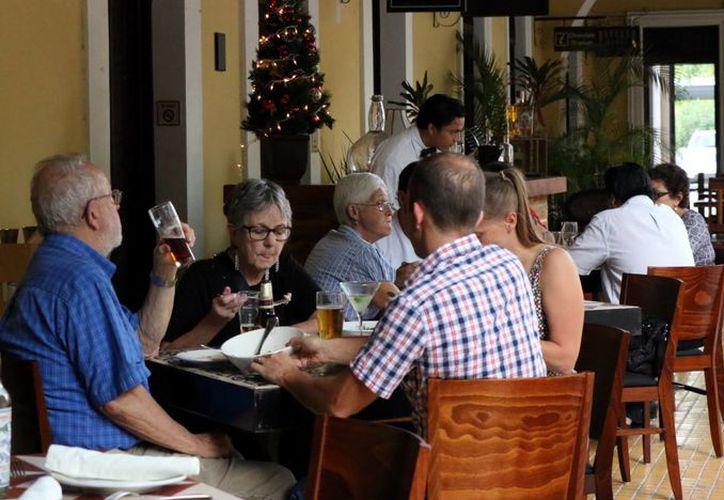 Los restaurantes del centro son visitados principalmente por turistas. Imagen de un grupo de visitantes que comen en un restaurante del centro de Mérida. (José Acosta/SIPSE)