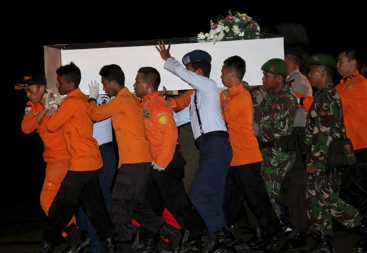 Rescatistas indonesios trasladan el cadáver de una de las víctimas del vuelo de AirAsia que cayó al mar de Java el domingo. (AP)