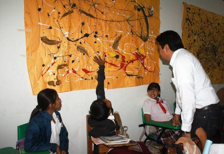 Pequeños de la escuela primaria 'Nicolás Bravo' de Motul enseñan al alcalde Julián Pech las obras desarrolladas en Educación Artística. (Cortesía)