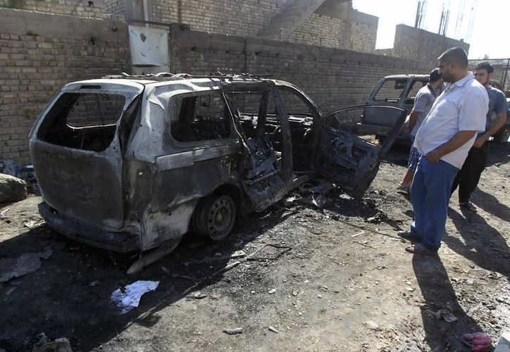 Un grupo de iraquíes inspecciona el lugar donde ayer explotó un artefacto, cerca de una mezquita chií, al este de Bagdag. (EFE)