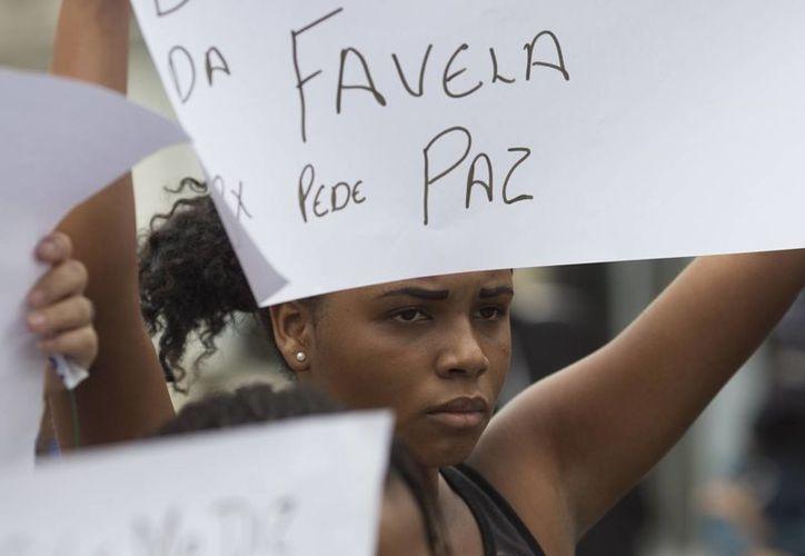 Una mujer levanta una cartulina con el mensaje 'la favela pide paz', escrito en portugués, durante el entierro de una mujer que murió por una bala perdida durante un tiroteo entre policías y narcotraficantes en una favela en Río de Janeiro. (Agencias)