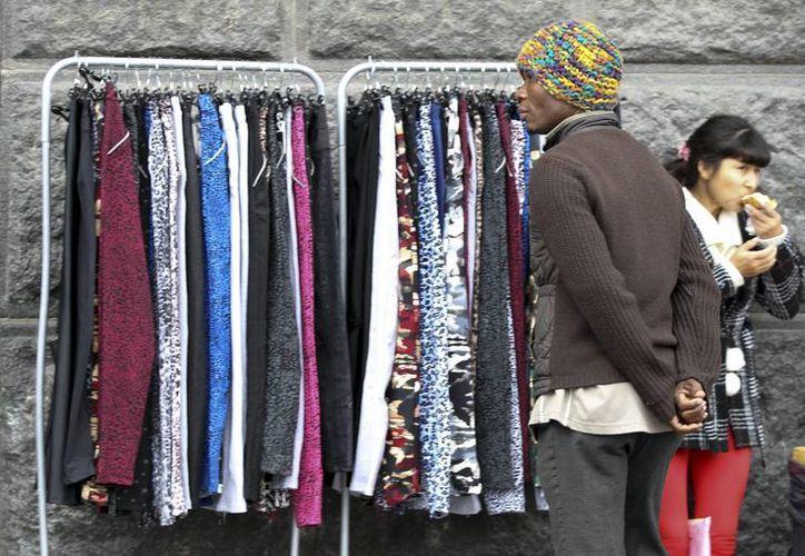 Un hombre observa ropa ofrecida por vendedores ambulantes por las calles del barrio popular de Flores, en Buenos Aires, Argentina. (EFE)