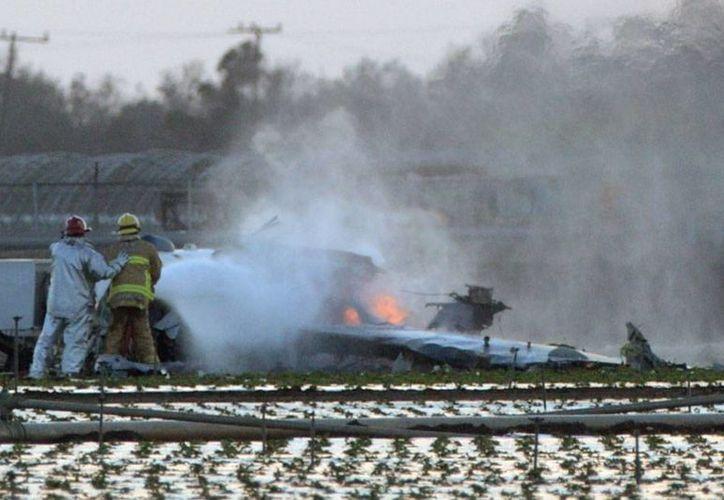 Bomberos intentan apagar el  fuego en los restos de un avión militar que se estrelló en una base naval de California, Estados Unidos. (AP)