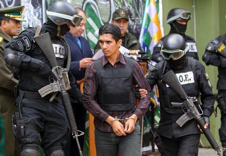 Miembros de la fuerza antinarcóticos custodian al capitán de la Fuerza Aérea Boliviana, Jimmy José Urzagaste Zabala, durante su presentación a los medios, este 4 de septiembre de 2015. (EFE).
