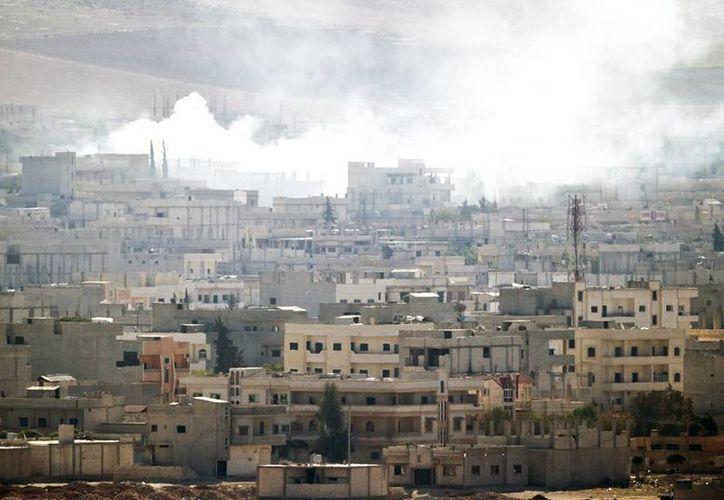 Columnas de humo se levantan sobre el pueblo sirio de Kobani en fotografía tomada desde las colinas del poblado turco de Suruc, cerca de la frontera entre ambos países. (Agencias)